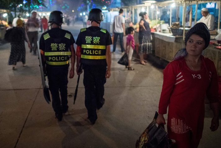 Police patrolling in a night food market near the Id Kah Mosque in Kashgar in China's Xinjiang Uyghur Autonomous Region, a day before the Eid al-Fitr holiday [JOHANNES EISELE/AFP/Getty Images]